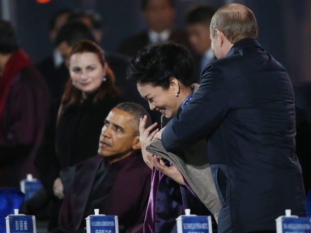 Scheiss auf die Etikette: Der russische Präsident Wladimir Putin legt der First Lady von China, Peng Liyuan, eine Wolldecke über die Schultern. Gut gemeint aber ein absolutes No-Go, einer chinesischen Frau so nahe zu kommen.