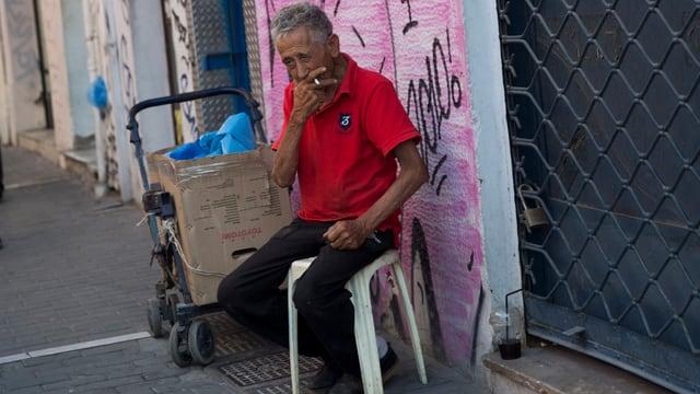 Ein Mann raucht am Strassenrand eine Zigarette.