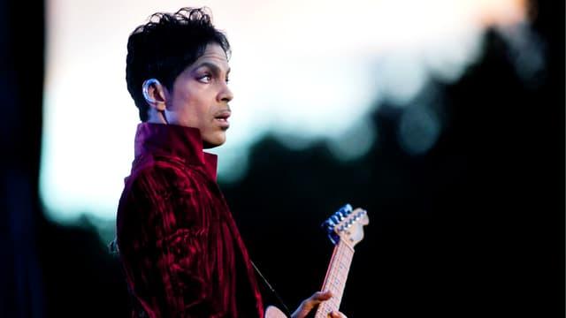 Ein Mann in einem Samtmantel spielt Gitarre (im Profil) un dmacht grosse Augen.