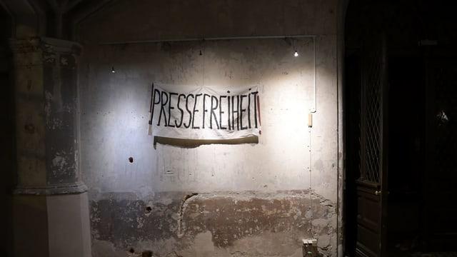 Purtret d'in placat cun scrit si «Pressefreiheit».