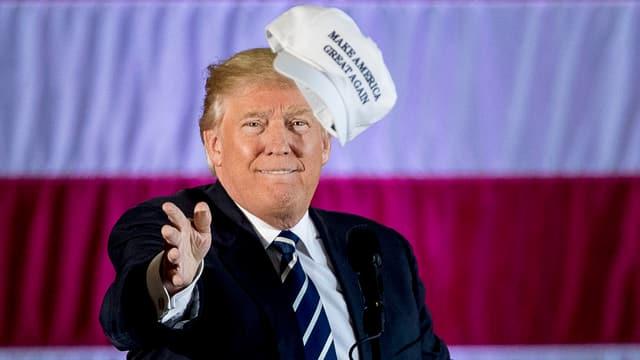 Trump wirft einen Hut in die Menge.