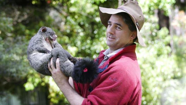 Ein Mann hält ein Opossum