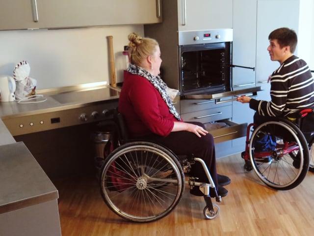 Junge Frau und junger Mann in Rollstühlen zeigen den tiefer liegenden Backofen.