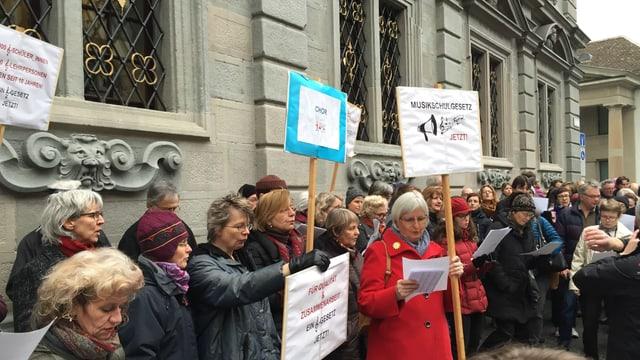 Befürworter des Musikschulgesetzes versuchen mit einem Lied und Plakaten das Kantonsparlament vor dem Rathaus noch umzustimmen.