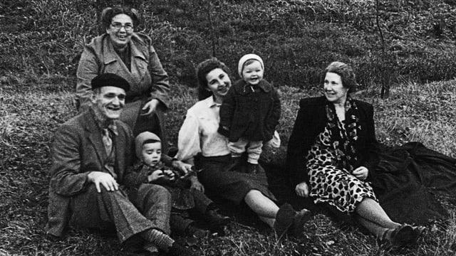 Familie mit zwei Kindern sitzt auf Rasen