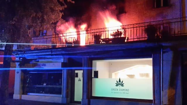 Flammen schlagen aus Fenstern einer Wohnung.