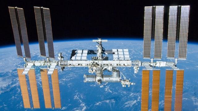 Ein Bild der Internationale Raumstation ISS auf dem im Hintergrund die Erde zu sehen ist.