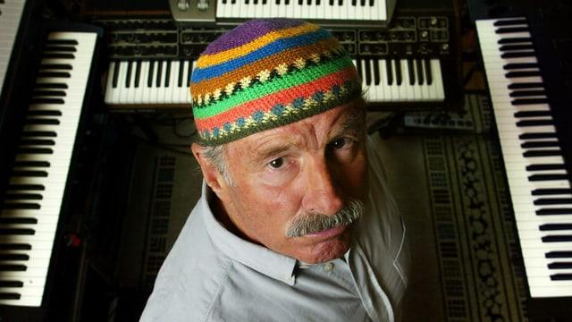 Blick von oben auf einen Mann mit einer bunten Mütze, der vor mehreren Keyboards steht und von unten in die Kamera schaut.