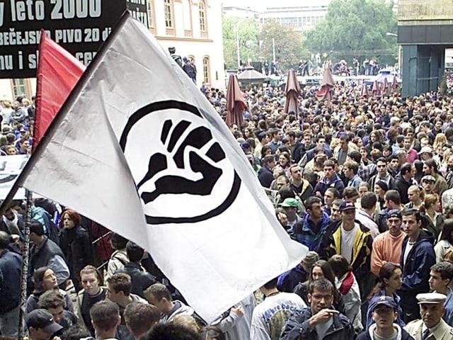 Die Fahne von «Otpor» weht über einer demonstrierenden Menschenmasse.