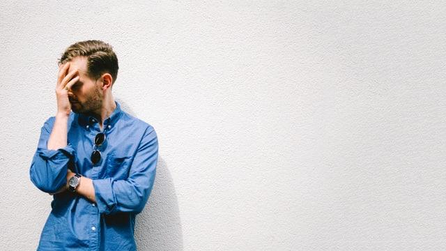 Mann mit Hand vor Gesicht in blauem Hemd vor weisser Wand