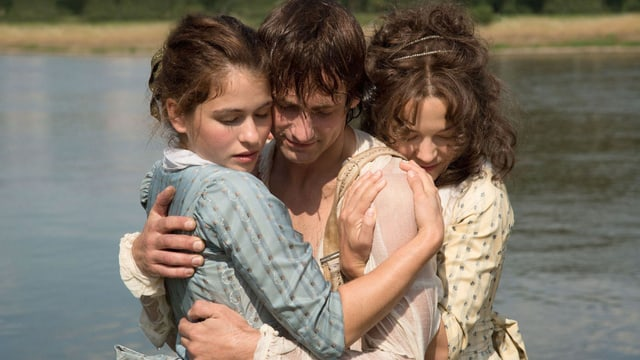 Ein Mann steht zwischen zwei Frauen, sie halten einander fest.