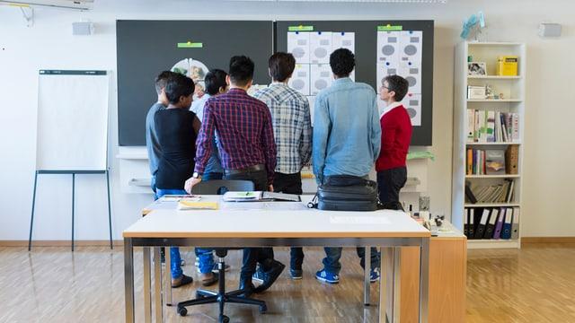 Schüler stehen in einem Klassenzimmer vor einer Tafel