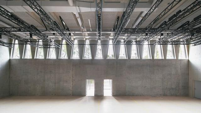 Innenansicht des Tanzhauses: Sichtbeton, zwei Türen und dreieckige Fenster, durch die Licht fällt.