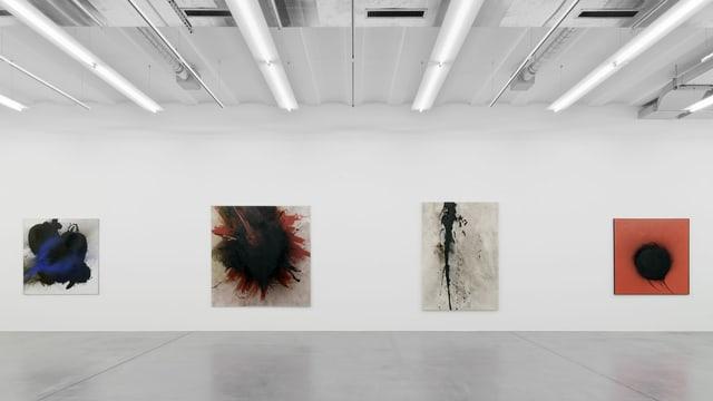 Vier Bilder hängen an einer Wand.