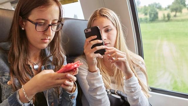 Zwei Mädchen im Zug mit Smartphones