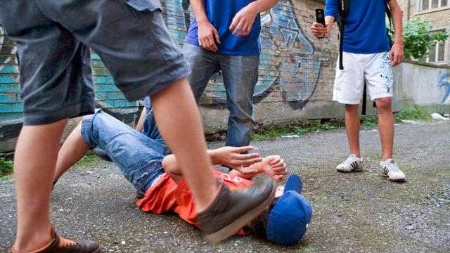 Jugendlicher liegt am Boden und wird traktiert