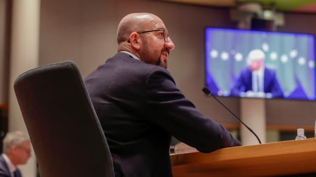 Charles Michel an einem Pult sitzend. Im Hintergrund eine Videowand.