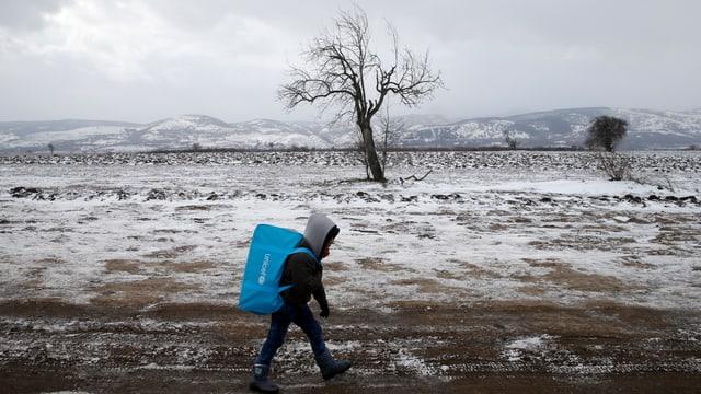Ein Flüchtlingskind läuft auf gefronenen Boden mit Rucksack über die Grenze.
