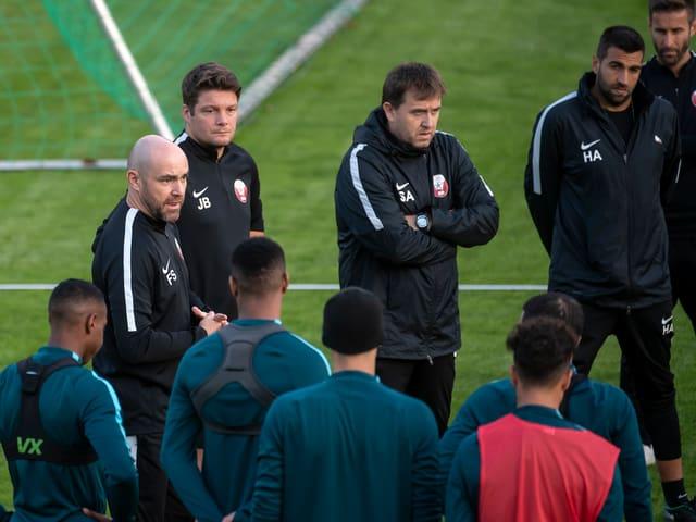 Katarische Nationalspieler stehen im Training zusammen.