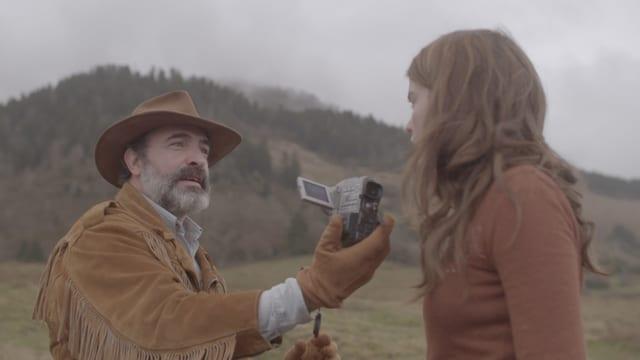 Ein Mann mit Hut und Lederjacke hält einer Frau eine Kamera entgegen.
