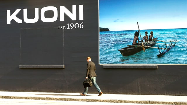 Werbeplakat der Firma mit polynesischen Ruderbootfahrern und einem Mann, der vor dem Plakat vorbeischreitet und zu Boden schaut.