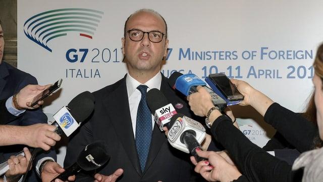 Alfano umgeben von Mikrofonen, die ihm Reporter hinstrecken.