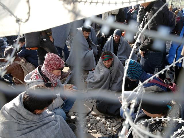 Menschen sitzen am Boden, eingehüllt in Wolldecken, hinter einem Drahtgeflecht mit Nato-Stacheldraht.