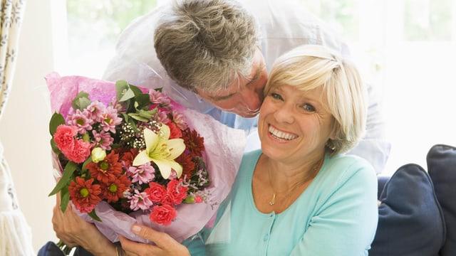 Ein Mann schenkt einer Frau einen Blumenstrauss und küsst sie auf die Wange