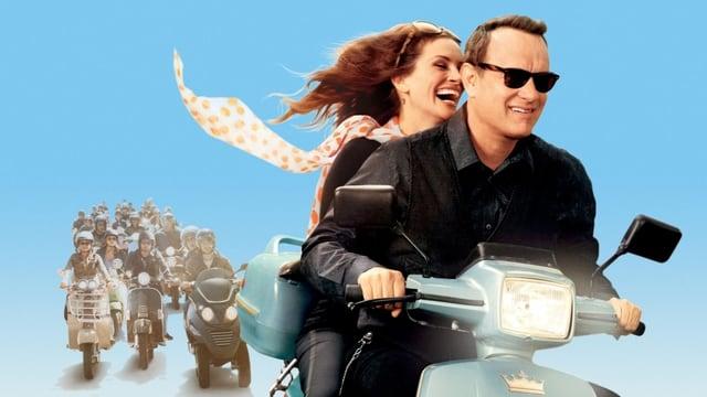 Ein Mann fährt auf einer Vespa. Mit ihm fährt eine Frau mit.