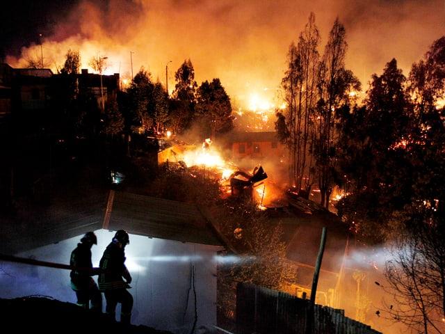 Feuerwehrmänner mit Löschschlauch. Im Hintergrund wütet der Brand.