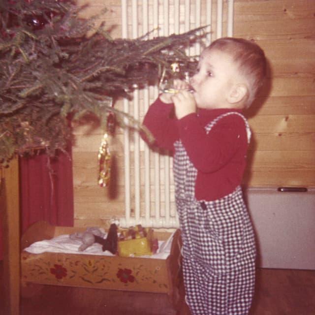 Ein kleiner Bub mit rotem Pullover und karierter Hose nascht Schokolade von einem Weihnachtsbaum.