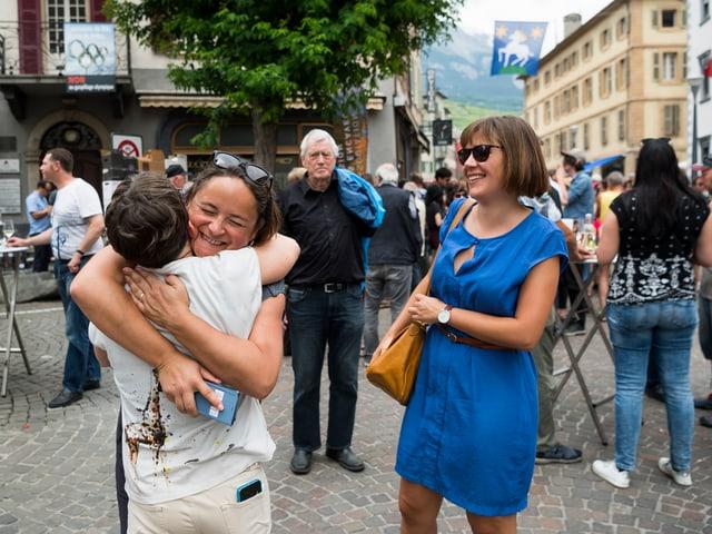 Die beiden Frauen und eine dritte, die Brigitte Wolf umarmt