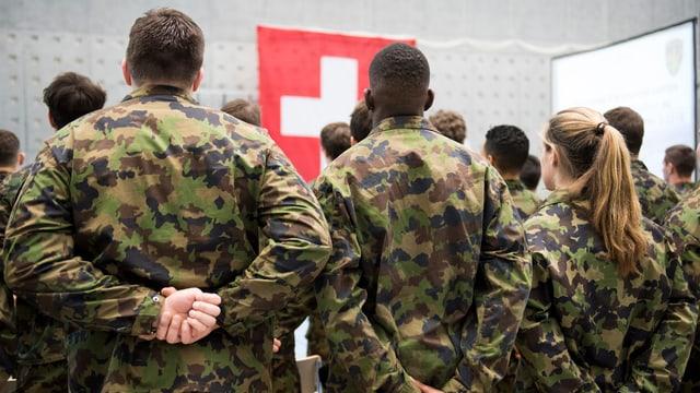 Soldaten von hinten, vor ihnen eine Schweizer Flagge.