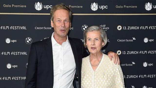 Ein Mann und eine ältere Frau lächeln in die Kamera