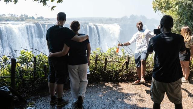 Touristen besuchen die Victoriafälle.