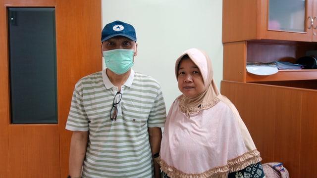 Ein Mann mit Mundschutz steht neben einer Frau.