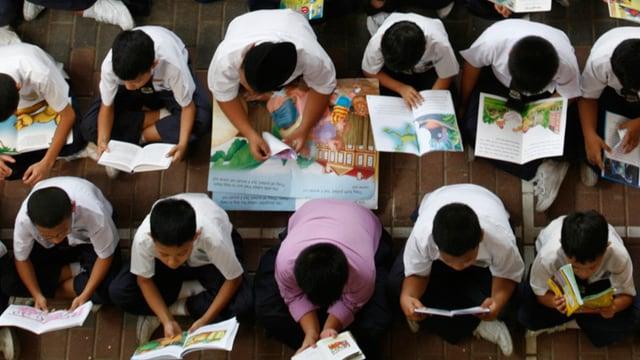 Aufsicht auf zahlreiche Kinder, die lesend am Boden sitzen.