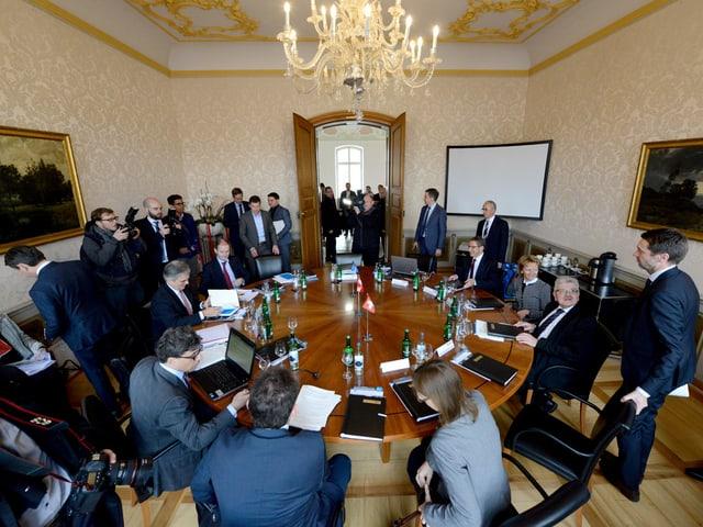 Runder Tisch in einem Sitzungszimmer im Regierungsgebäude voll mit Leuten