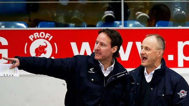 Dus umens, trenaders da hockey sin glatsch, guardan encunter sanester e dattan instrucziuns