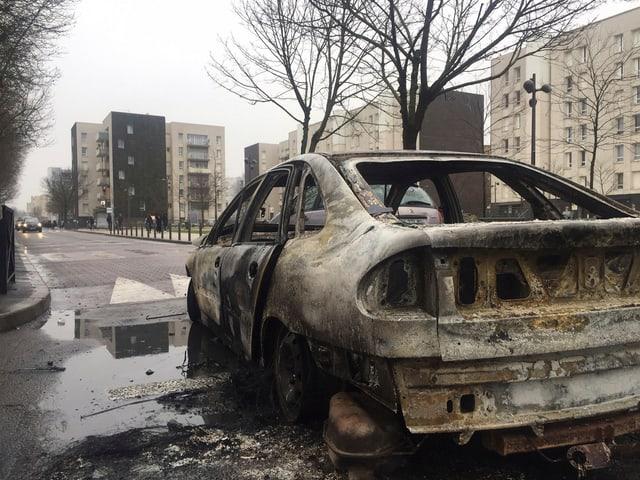 Ein ausgebranntes Auto vor der tristen Kulisse der Pariser Vorstadt Aulnay-sous-Bois.
