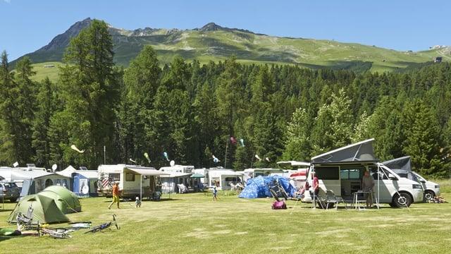 Viele Zelte, Wohnwagen und Wohnmobile auf einer Wiese.