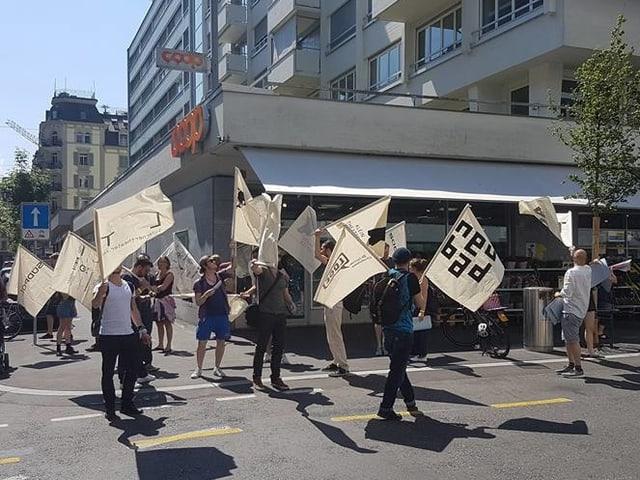 Eine Gruppe von Leuten zieht mit weissen Fahnen durch die Stadt Luzern.