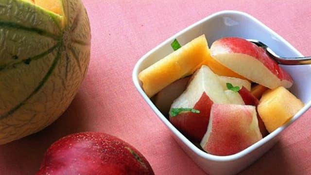 Kleine SChüssle mit Melonen-Nektarinen-Salat, dabenen eine Melone und eine Nektarine