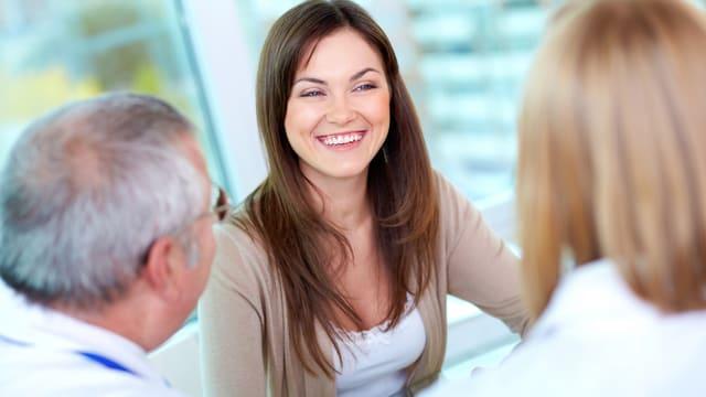 Eine Frau lacht einen Mann und eine Frau an.