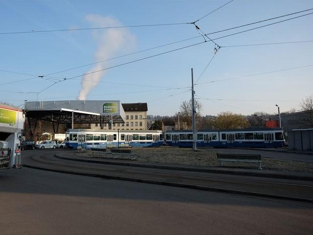 Ein blau-weisses Tram, im Hintergrund links im Bild die Entsorgungsstelle.