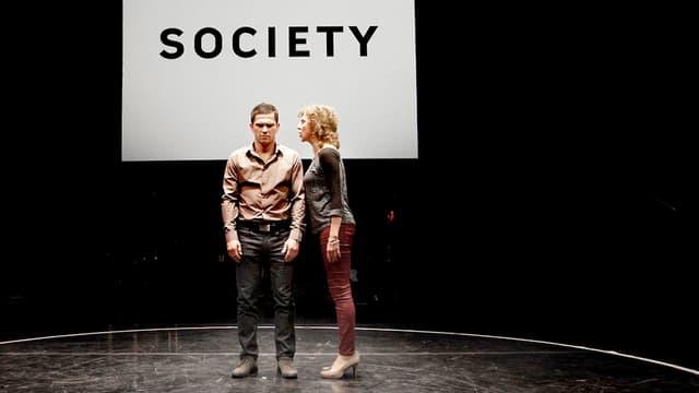Mann und Frau stehen in einem Kreis, darüber ein Plakat mit der Aufschrift Society.