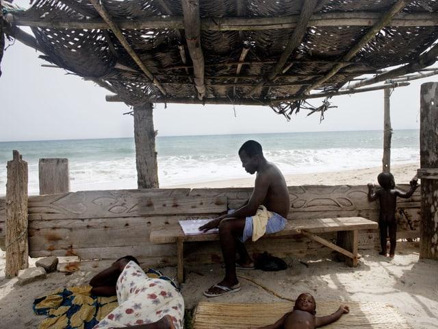 Eine Familie in einem Verschlag mit Dach am Strand. Die Frau und ein kleines Kind liegen auf Matten im Sand. Der Mann sitzt auf einer Bank und liest.