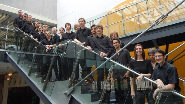 Ein Gruppe von Männern und Frauen, die von unten bis oben auf einer Treppe stehen.