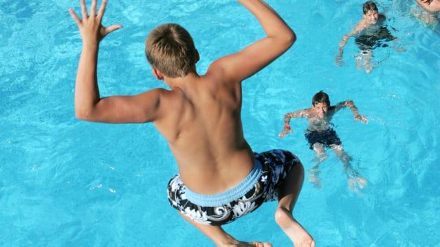 Ein Junge springt in einem Becken ins blaue Wasser