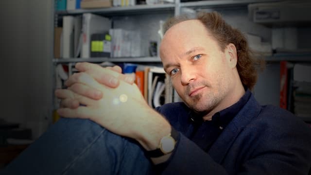 Regisseur Christian Frei sitzend vor einem Regal.